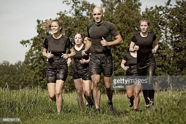 group of friends jogging outdoors during mud run - barracks stock pictures, royalty-free photos & images