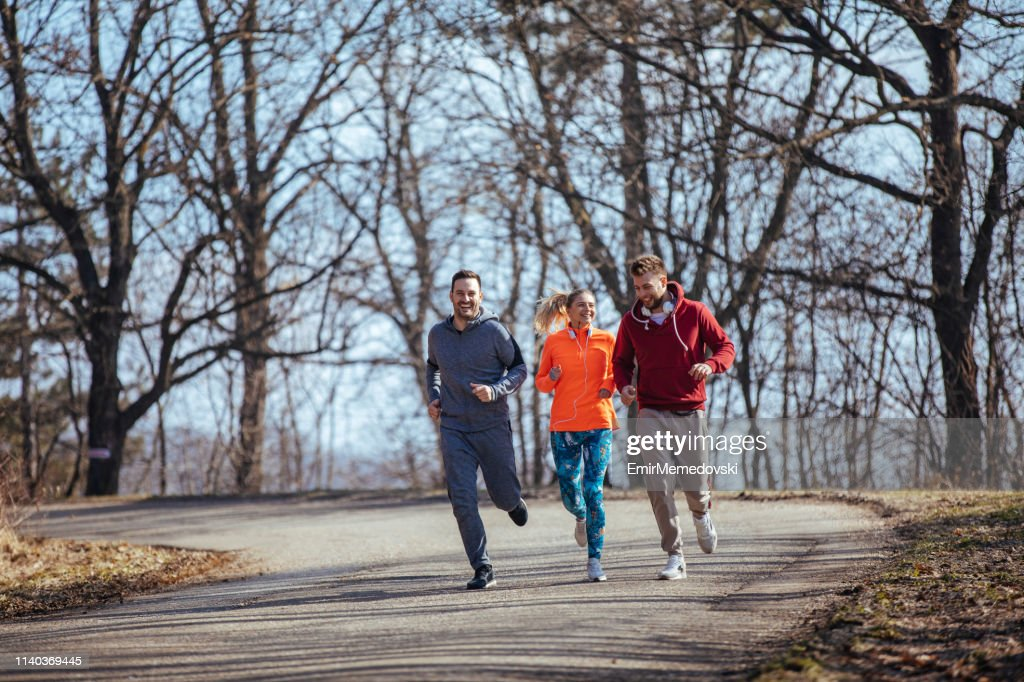 Group of friends jogging together outdoors : Stock Photo