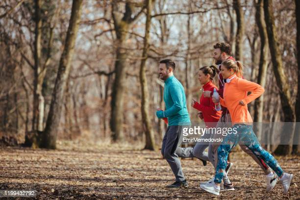 group of friends jogging together outdoors - warm up exercise stock pictures, royalty-free photos & images