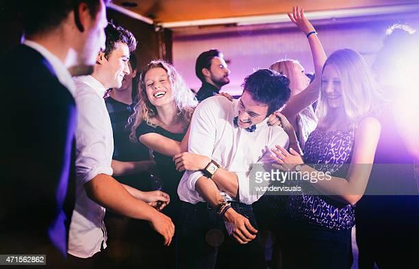 Group of friends joking around on the dance floor