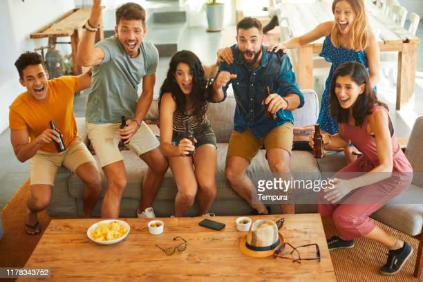 group of friends jump in joy when their team scores a goal. - guardare con attenzione foto e immagini stock