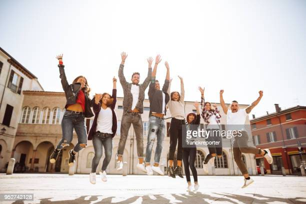 group of friends jumping all together on the city - gruppo di persone foto e immagini stock