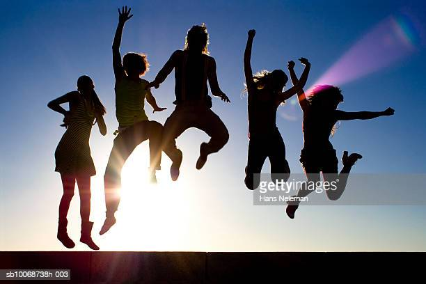 Group of friends jumping at beach, silhouette