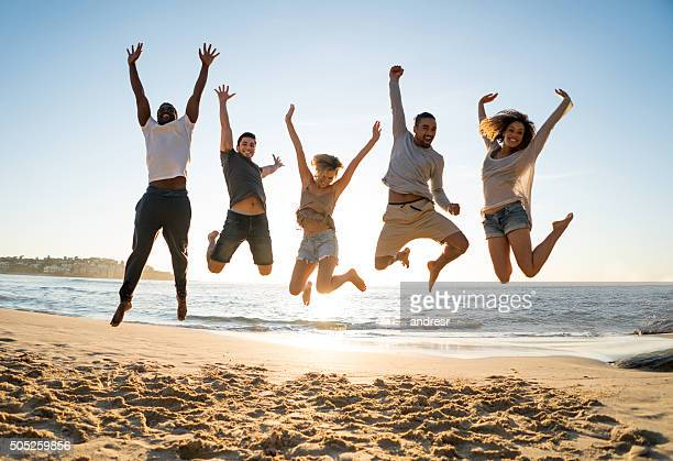 Group of friends jumping at the beach