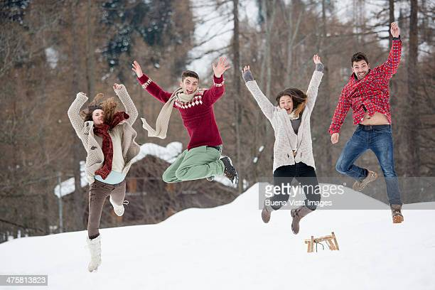 Group of friends jumping in snow