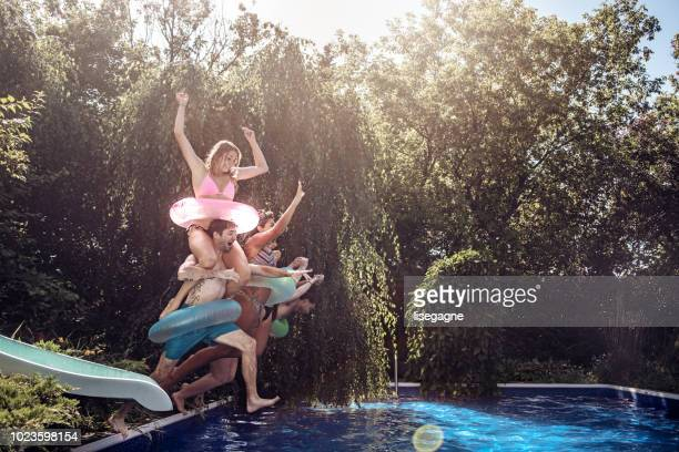 Group of friends jumping in the pool