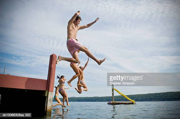 group of friends jumping into lake - finger lakes stock pictures, royalty-free photos & images