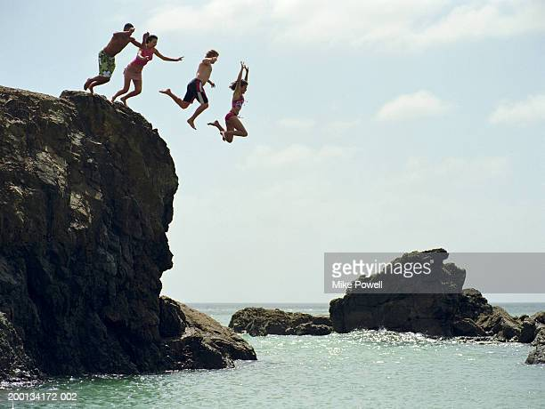 group of friends jumping into ocean from rock cliff - jumping stock pictures, royalty-free photos & images
