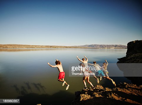 Group of friends jumping off cliff into river