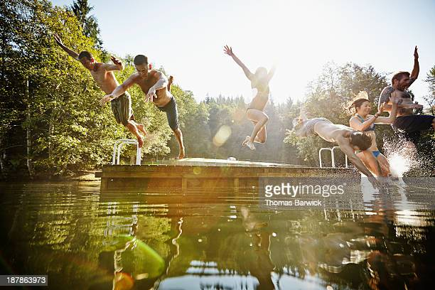 Group of friends jumping off dock into lake