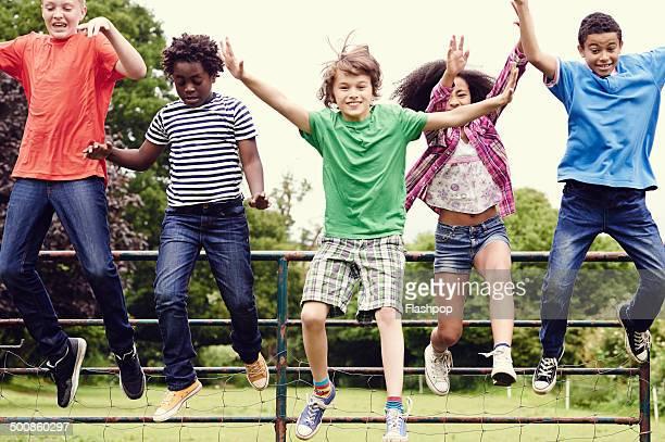 group of friends jumping off fence gate - somente crianças imagens e fotografias de stock
