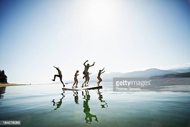 Group of friends jumping off floating dock