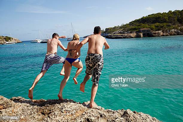 Group of friends jumping off rock into sea