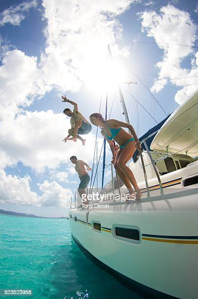 Group of friends jumping off sailboat into sea