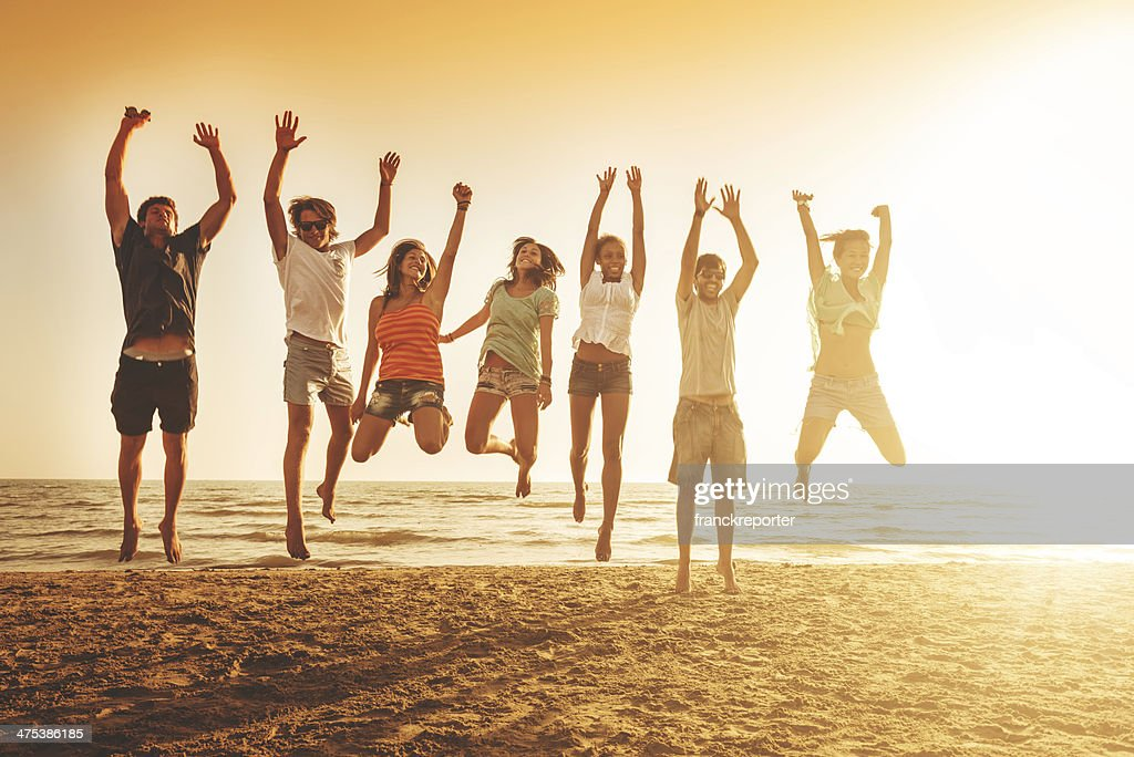 group of friends jumping on the beach : Stock Photo