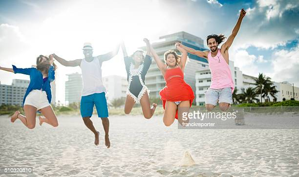 group of friends jumping on the beach