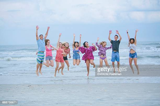 Group of friends (16-17) jumping playfully on beach