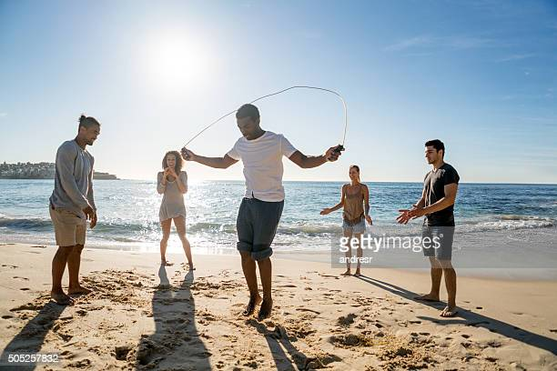 Group of friends jumping rope at the beach