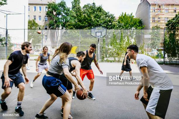 Group Of Friends Keeping Fit Playing Basketball Together