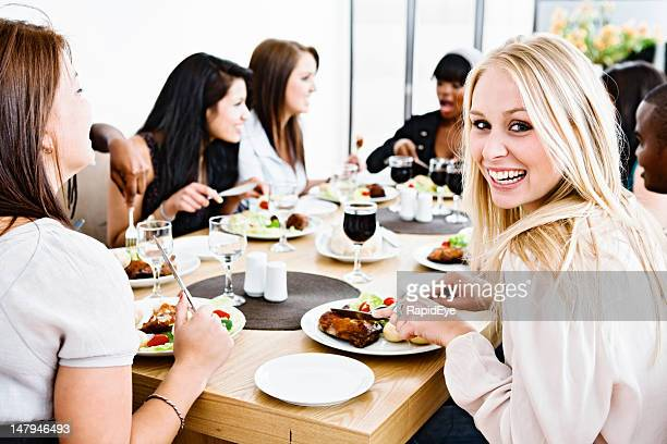Group of friends laugh and chat together round dining table
