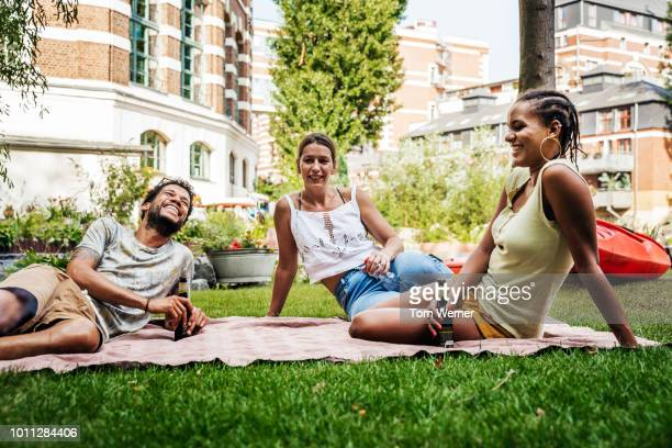 Group Of Friends Laughing And Drinking By Canal Together