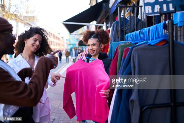 group of friends laughing trying on vintage clothing outside a store - clothing stock pictures, royalty-free photos & images
