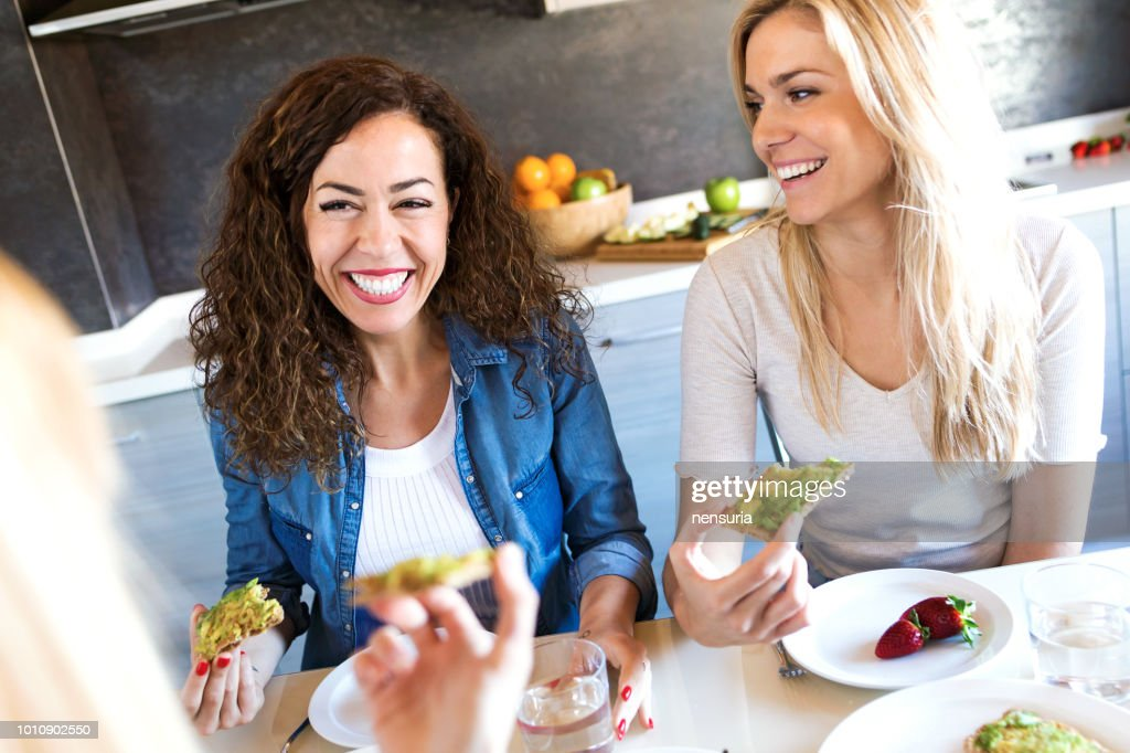 Group of friends laughing while eating healthy food at home. : Stock Photo