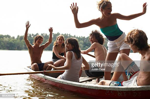 Group of friends laughing while sitting in boat