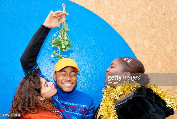 group of friends laughing with mistletoe - mistletoe stock photos and pictures