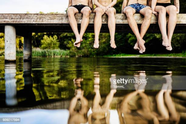 group of friends legs dangling off jetty - pier stock pictures, royalty-free photos & images
