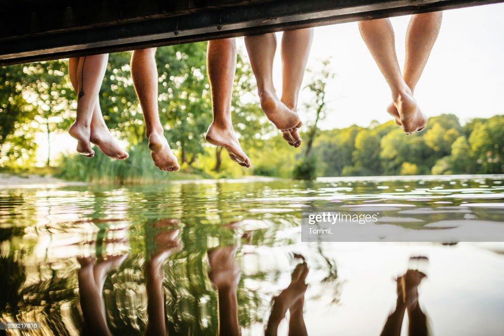 Gruppe von Freunden Beine baumeln ab Anlegestelle : Stock-Foto
