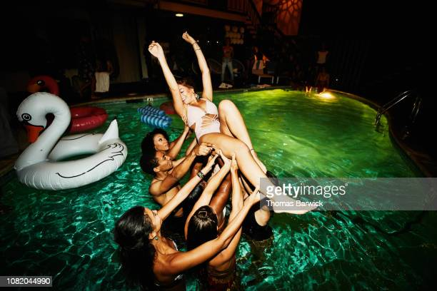 group of friends lifting woman into the air during party in hotel pool - naughty america foto e immagini stock
