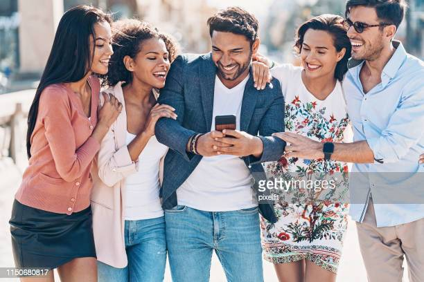 group of friends looking at a smart phone - cinco pessoas imagens e fotografias de stock