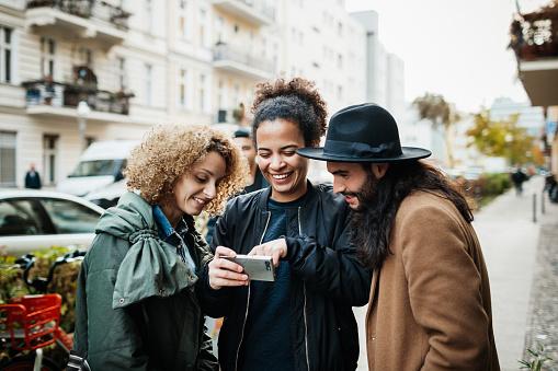 Group Of Friends Looking At Smartphone In Street - gettyimageskorea