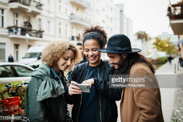 group of friends looking at smartphone in street - three people stock pictures, royalty-free photos & images