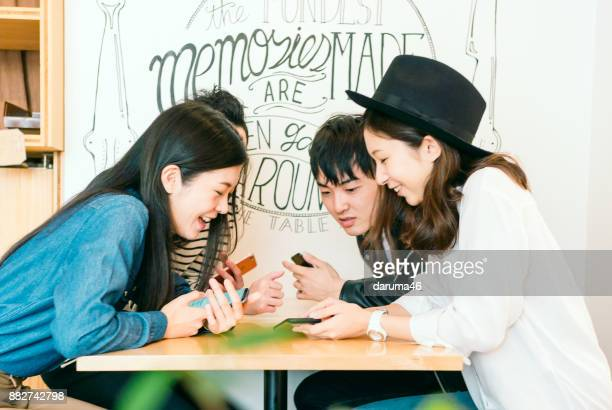 group of friends looking at smartphones - east asia stock pictures, royalty-free photos & images