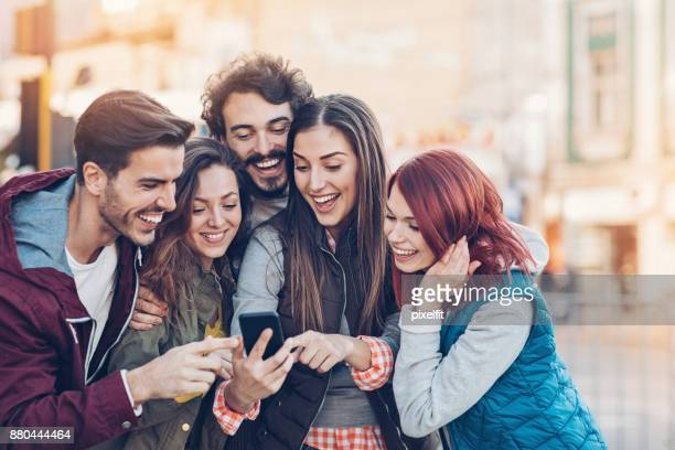 Group of friends looking at the phone and pointing