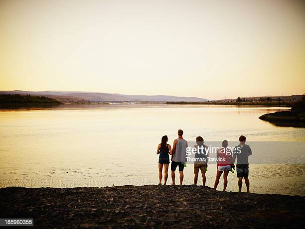 group of friends looking out over river at sunset - vijf personen stockfoto's en -beelden
