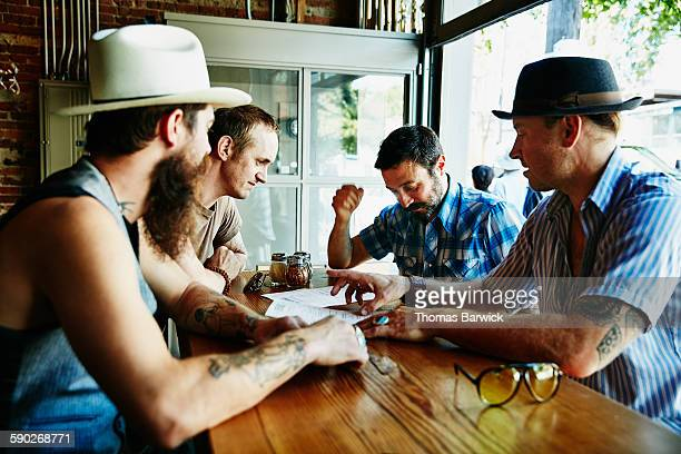 Group of friends looking over menu in restaurant