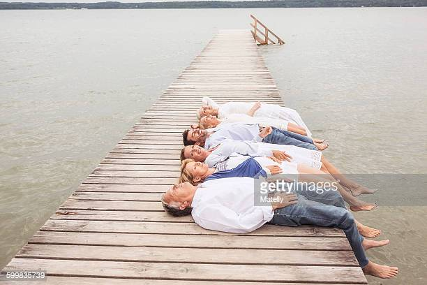 Group of friends lying in a row, on pier