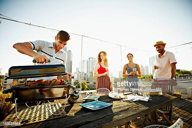 Group of friends making dinner on rooftop deck