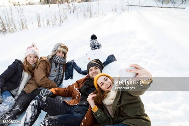 Group of friends making selfie with snowman.