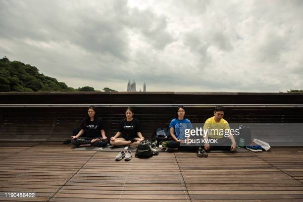 A group of friends meditate as the moon moves in front of the sun in a rare ring of fire solar eclipse in Singapore on December 26 2019
