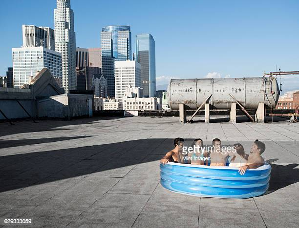 A group of friends, men and women sitting in a small inflatable water pool on a city rooftop, cooling down.