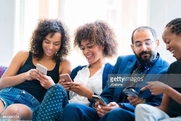 自分の携帯電話をチェックすべての仕事からの脱却の友人のグループ