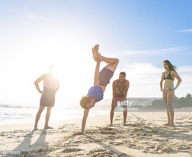 Group of friends on beach watching friend do handstand