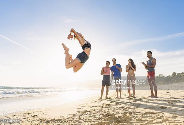 Group of friends on beach watching friend leap in air