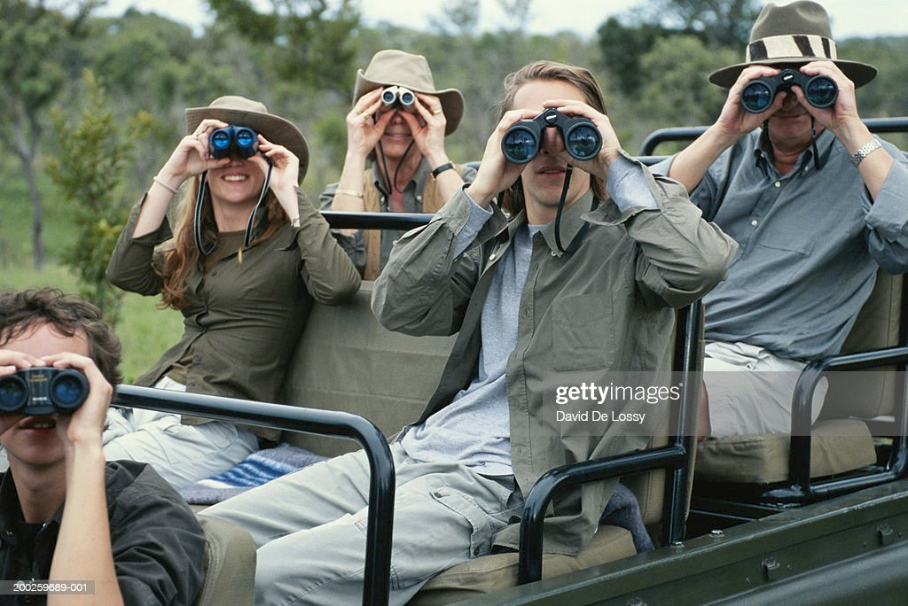Group of friends on off road vehicle with binoculars : Stock Photo