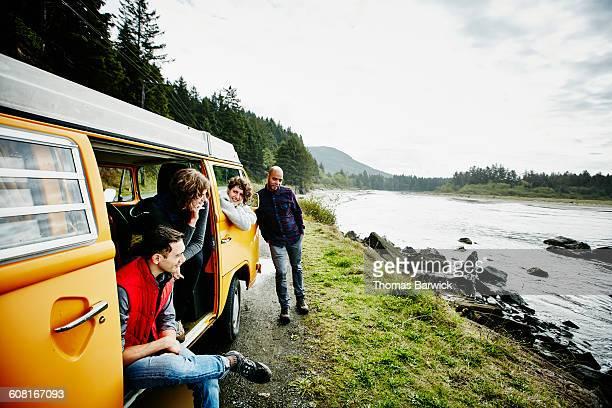 group of friends on road trip parked by ocean - landvoertuig stockfoto's en -beelden