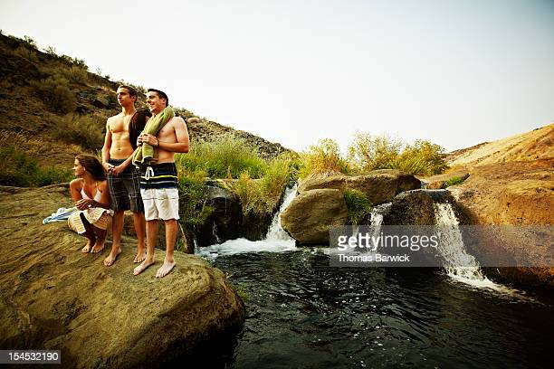 Group of friends on rock near swimming hole
